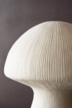 Close-up detail image of the mushroom top on the White Sandstone Mushroom Table Lamp when not lit up on a dark wall background