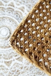 Contrast image of the natural Modern Woven Rattan Dining Chair against the RSG white mandala round rug
