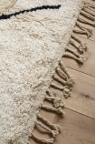 Close-up detail image of the tassels on the Original Moroccan Berber Large Rug on pale wooden floor