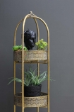 detail image of Ornate Gold Tall Tray Shelves with plants and black face ornament on top shelf with grey wall background