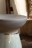 Close-up detail image of join on the Pablo Dipped Black Stool  with armchair in background