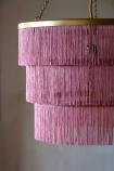 Close-up lifestyle image of the Pink Three-Tier Fringe Chandelier