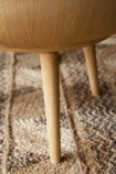Close up detail image of the legs on the Oak Curve Coffee Table With Removable Lid on woven rug flooring