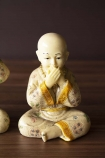 Close-up detail image of the Speak No Evil Monk on wooden surface and dark wall background