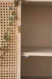 Close-up of the shelf inside the Sungkai Woven Cane & Mango Wood Oval Cabinet