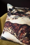 Close-up detail image of the Sleeping Tiger Velvet Cushion on ochre gold velvet chair with dark wall background