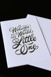 detail image of Welcome to the World Little One Greeting Card - Pink pink with gold writing with envelope on black table