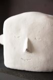 Close-up detail image of the White Concrete Stan Statue on black mantel and dark wall background