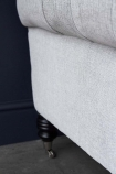 Close-up image of the wooden leg & caster on the Soft Grey Modern Chesterfield 3 Seater Sofa