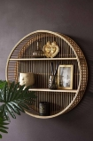 Lifestyle image of the Round Bamboo Two-Tier Shelf Unit hanging on dark wall filled with home accessories and house plant in foreground