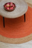 lifestyle image of Round Faro Jute Rug - 4 Colours Available with round coffee table and fruit bowl on top