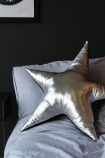 lifestyle image of Sarah Baily Metallic Silver Leather Star Cushion on bed with grey bedding and dark wall background