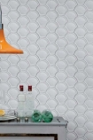 lifestyl eimage of Scales Wallpaper with grey table with bottles on and orange ceiling light