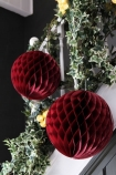 lifestyle image of Set Of 2 Honeycomb Ball Decorations - Burgundy on staircase Bannister with ivy