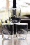Lifestyle image of all 3 recycled glass water tumblers on pale wood table with windows in background