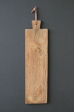 lifestyle image of one of Set Of 3 Teak Paddle Breadboards hung on grey wall