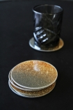 lifestyle image of Set Of 4 Gold Glitter Coasters - Small stacked with one with black glass on and on black table