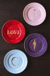 lifestyle Image of the Set Of 4 Love & Lightening Plates on black surface background