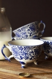 Lifestyle image of the Set Of 4 Pretty Indigo Blue & White Teacups on a shelf with milk bottle in background and dark wall background