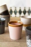 lifestyle image of Set Of 6 Earthenware Tumblers - Style 2 on wooden table with patterned wallpaper in background