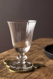 Lifestyle image of the Ribbed Glass Wine Glass on a coaster on wooden surface with dark wall background
