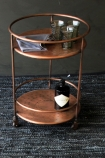 lifestyle image of Antique Copper Shoreditch Drinks Trolley with Hendricks gin bottle and glasses with black rug flooring and dark grey wall background