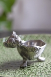 Image of the Cuddly Bear Silver Egg Cup on green plate and plant in background lifestyle