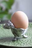 Image of the Cuddly Bear Silver Egg Cup with an egg in it on green plate and plant in background lifestyle