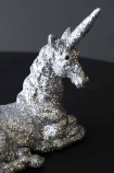 detail image of Silver Sparkle Unicorn Ornament on black table with grey wall background
