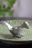 lifestyle Image of the Squirrel Silver Egg Cup on green plate and plant in background