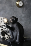 lifestyle image of Sitting Monkey Table Lamp - Black - Suitable For Outdoors on black and gold side table with black and white cowhide armchair and gold clock on grey wall background
