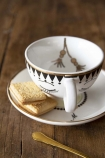 lifestyle image of Sleeping Face Teacup & Saucer with gold spoon and custard creams on wooden table