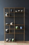 Standing brass industrial storage rack with crockery on each shelf with dark background and wooden floor lifestyle image
