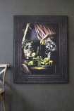 lifestyle image of Still Life Canvas Print - Yellow on grey wall with chair in corner