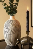 Lifestyle image of the Stone & Black African Ceramic Bottle Vase with eucalyptus inside and armadillo candle holder and lit candle with cloisters painted wall background
