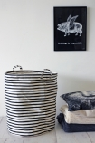 lifestyle image of Striped Laundry/Storage Basket - Large with folded blankets on white wooden flooring and pig with wings art print on white wall background