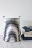 lifestyle image of Striped Laundry/Storage Basket - Large with folded blankets on white wooden flooring and white wall background