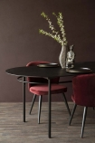 Angled lifestyle image of the Sungkai Wood Black Oval Dining Table with red dining chairs and vase with briarwood painted wall background and dark wooden flooring