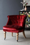 lifestyle image of Swedish Red Velvet Boudoir Cocktail Chair with patterned cabinet with ornaments on top and grey wall background