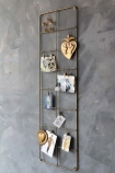 lifestyle image of Tall Brass Wall Frame with postcards, pictures and ornaments on hung on distressed grey wall background
