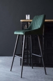 lifestyle image of Tall Casino Velvet Bar Stool - Rich Green next to bar with grey flooring and dark wall background