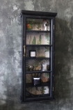 lifestyle image of Tall & Slim Distressed Black Wall Cabinet with Botanical Lining on distressed wall background