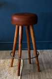 lifestyle image of Tapas Bar Leather Stool - Tall on rattan rug and wooden flooring with dark blue wall background