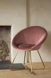 Lifestyle image of The Grand Velvet Circular Dining Chair in Rose Pink next to fire place on wooden flooring and pale wall background
