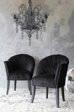 lifestyle image of The Lovers Velvet Chair - Back to Black with black wire chandelier above and grey wall background