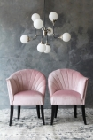 lifestyle image of The Lovers Velvet Chair - Blush Pink with white globe ceiling light above and grey wall background