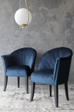 lifestyle image of The Lovers Velvet Chair - Midnight Blue with white and gold ceiling light and grey wall background