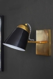 Lifestyle image of the black version of the The Mortimore Wall Light on dark grey wall background