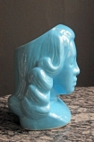 detail image of side of Tiki Lady Cocktail Cup / Display Vase blue lady face on marble effect table and grey wall background