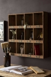 Lifestyle image of the Traditional Pigeon Hole Wooden Storage Wall Unit filled with accessories on dark wall background and above wooden desk